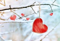 Corazón rojo de madera en rama de árbol nevosa en invierno Fotografía de archivo