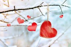 Corazón rojo de madera en rama de árbol nevosa en invierno Imágenes de archivo libres de regalías