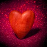 Corazón rojo de madera en un fondo borroso Imagen de archivo libre de regalías