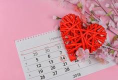 Corazón rojo de mimbre hermoso con las flores rosadas en un fondo rosado Fotos de archivo libres de regalías