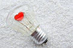 Corazón rojo de un bulbo eléctrico imagenes de archivo