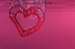 Corazón rojo del alambre que cae en el agua Fotografía de archivo