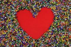 Corazón rojo del amor en granos coloridos Fotografía de archivo libre de regalías