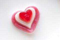 Corazón rojo del caramelo en un fondo de la leche Fotos de archivo libres de regalías