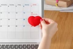 Corazón rojo del control de Famale en calendario Fotos de archivo libres de regalías