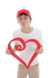 Corazón rojo del muchacho adolescente que frunce encima de besar a la tarjeta del día de San Valentín Imagen de archivo