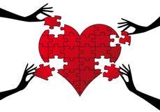 Corazón rojo del rompecabezas con las manos Foto de archivo libre de regalías