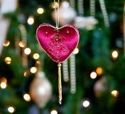 Corazón rojo del terciopelo delante del árbol de Navidad Imagen de archivo libre de regalías