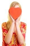 Corazón rojo delante de la cara femenina Imágenes de archivo libres de regalías