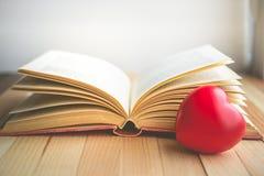 corazón rojo delante del libro abierto con el espacio de la copia en humor de la relajación Foto de archivo libre de regalías