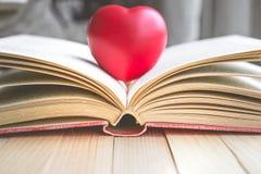 Corazón rojo en el libro abierto con el espacio de la copia en la relajación y el MES acogedor Imágenes de archivo libres de regalías