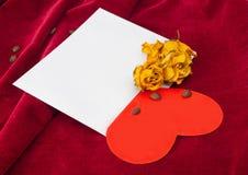 Corazón rojo en el sobre con las rosas y los granos de café secados Imagen de archivo libre de regalías