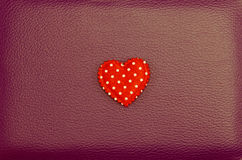 Corazón rojo en fondo de cuero rojo del vintage Imagen de archivo libre de regalías