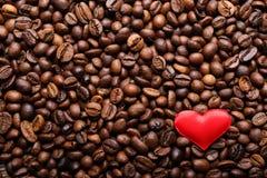 Corazón rojo en fondo de los granos de café Fotografía de archivo