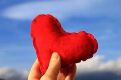 Corazón rojo en la mano de la mujer con el cielo azul en el fondo, el día de tarjeta del día de San Valentín Fotografía de archivo libre de regalías