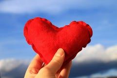Corazón rojo en la mano de la mujer con el cielo azul en el fondo, el día de tarjeta del día de San Valentín Fotografía de archivo