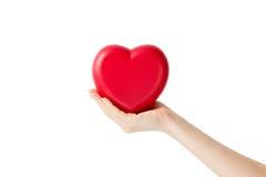 Corazón rojo en la mano de la mujer, en el primer blanco del fondo fotos de archivo