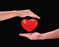 Corazón rojo en la mano de un hombre. Fotografía de archivo libre de regalías