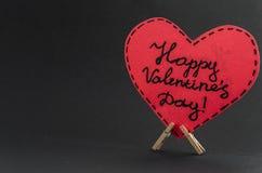 Corazón rojo en la pinza con el día de tarjetas del día de San Valentín feliz del saludo en fondo oscuro Imagen de archivo