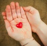 Corazón rojo en las manos Imágenes de archivo libres de regalías