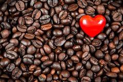 Corazón rojo en los granos de café Imágenes de archivo libres de regalías