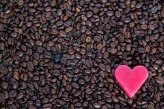 Corazón rojo en los granos de café Imagen de archivo