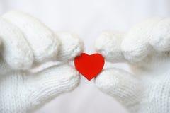 Corazón rojo en los guantes blancos Fotos de archivo