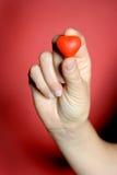 Corazón rojo en mano femenina Imagenes de archivo