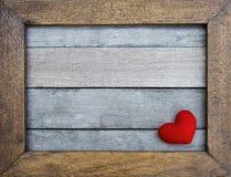Corazón rojo en marco de madera en el fondo de madera Fotos de archivo