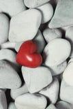 Corazón rojo en piedras del guijarro, aún vida Día de tarjetas del día de San Valentín y fondo de los amantes Imágenes de archivo libres de regalías