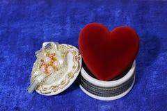 Corazón rojo en rectángulo abierto en el terciopelo azul Foto de archivo