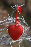 Corazón rojo en un fondo del alambre de púas Foto de archivo