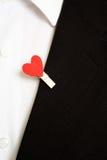 Corazón rojo en un traje negro Foto de archivo libre de regalías