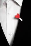 Corazón rojo en un traje negro Imagen de archivo libre de regalías
