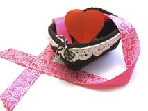 Corazón rojo en una cesta con la cinta rosada Fotografía de archivo