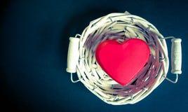 Corazón rojo en una cesta de mimbre blanca Foto de archivo