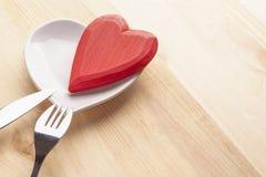 Corazón rojo en una placa blanca bajo la forma de corazón en un fondo de madera con una bifurcación y un cuchillo imagen de archivo