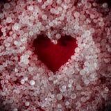 Corazón rojo formado de pequeños cristales redondos de la sal imagen de archivo libre de regalías