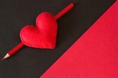 Corazón rojo hecho del fieltro en un fondo negro Imágenes de archivo libres de regalías