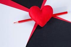 Corazón rojo hecho del fieltro en un fondo negro Imagen de archivo libre de regalías