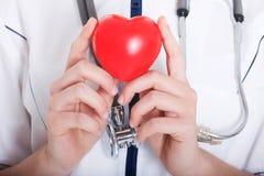 Corazón rojo llevado a cabo por un doctor de sexo femenino Foto de archivo libre de regalías