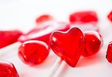 Corazón rojo macro con los chocolates y las piruletas en el fondo blanco Imagen de archivo libre de regalías