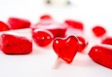 Corazón rojo macro con los chocolates y las piruletas en el fondo blanco Fotografía de archivo