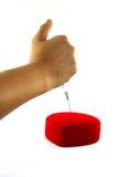 Corazón rojo perforado en un fondo blanco Imagen de archivo libre de regalías