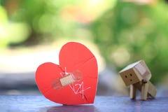 Corazón rojo roto con cosido otra vez en fondo verde natural fotografía de archivo libre de regalías