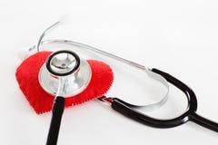 Corazón rojo y un estetoscopio en el fondo blanco Imágenes de archivo libres de regalías