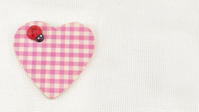 Corazón rosado de la tela escocesa en el fondo blanco Imagenes de archivo