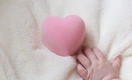 Corazón rosado en la mano de un niño Fotos de archivo