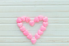 Corazón rosado en un fondo blanco de madera Fotos de archivo