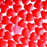 Corazón rosado entre una pila de corazones rojos. Fondo de los corazones del caramelo Imagenes de archivo